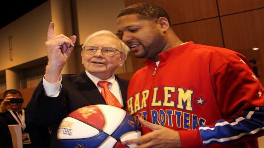 Warren Buffett pals around with the Harlem Globetrotters at the Berkshire Hathaway Annual ShareHolders Meeting in Omaha, Nebraska.